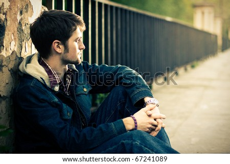Young man sitting near the fence in sunlight