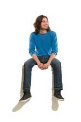 Young man sitting on a banner, smiling and looking away. Full length studio shot isolated on white.