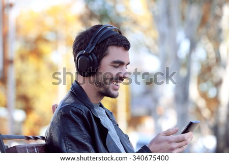 Young man sitting on a bench in park and listening to music #340675400