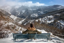 Young man sitting on a bench on the side of a mountain enjoying a snowy landscape in the background in winter. Freedom concept.