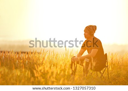 Young man sitting on a chair in the grass field during the sunset. #1327057310