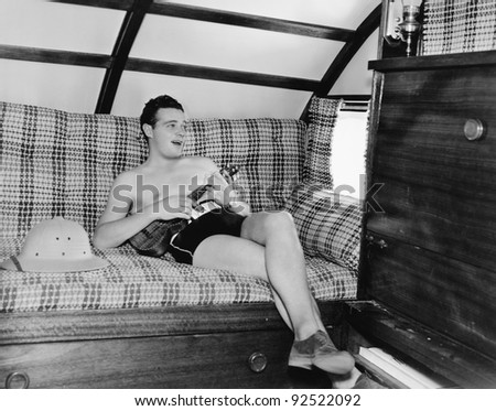 Young man sitting on a couch and playing a guitar