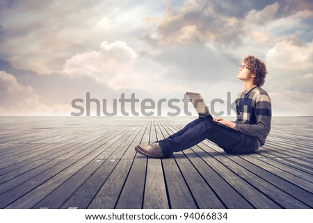 Young man sitting on a parquet floor and using a laptop - stock photo