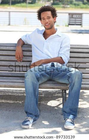 Young man sitting on a riverside bench
