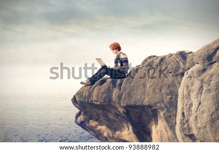Young man sitting on a rock ad using a laptop