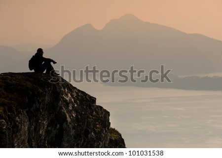 Young man sitting on a rock and looking to a valley below