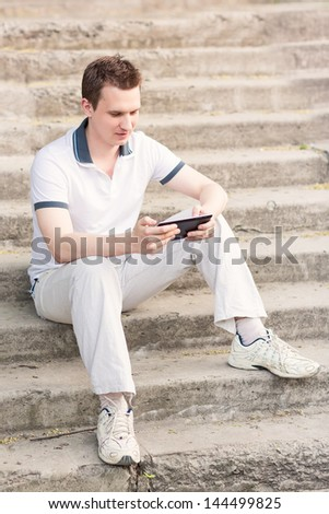 Young man sitting on a stairs with tablet pc outdoor