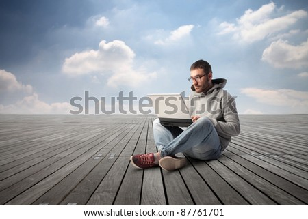 Young man sitting on a wooden floor and using a laptop