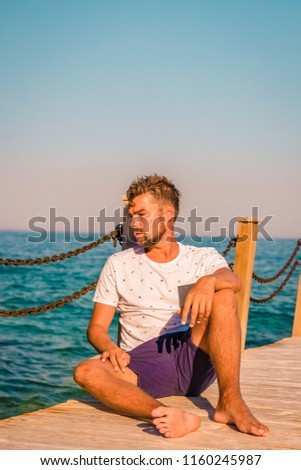young man sitting on a wooden pier with dreamy look over ocean of Fethiye Turkey