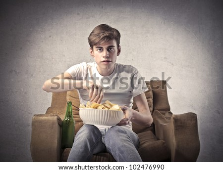 Young man sitting on an armchair with a beer beside him and a bowl of chips on his knees