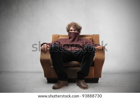 Young man sitting on an armchair with turtleneck sweater on his mouth