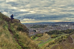 Young man sitting on Arthur's Seat, photographing the city of Edinburgh, Scotland. Foreground of Salisbury crags, and in the backgrounds, houses and roofs with Edinburgh castle.