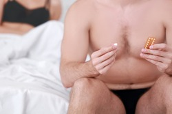 Young man sitting on bed with birth control pills and vaginal suppository. Concept of choosing the contraceptive method