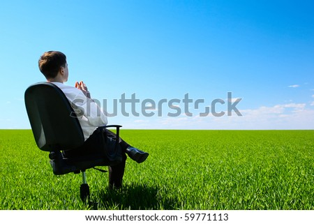 Young man sitting on chair in green meadow