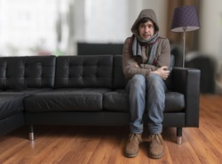 Young man sitting on couch is feeling cold at home.