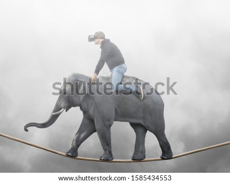 Young man sitting on elephant with vr glasses balancing walking on rope