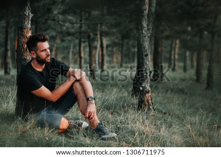 Young man sitting on grass in the woods contemplating