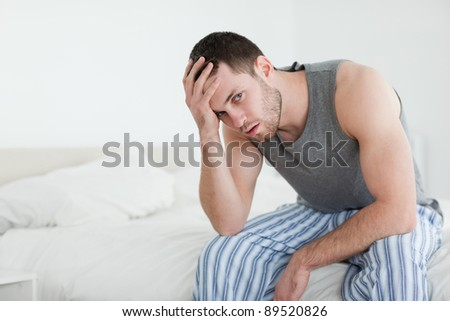 Young man sitting on his bed while looking at the camera