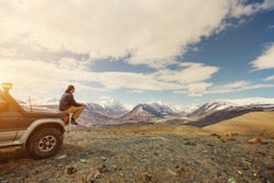 Young man sitting on his car in beautiful mountains landscape. Off-road travel vacation, enjoy  freedom