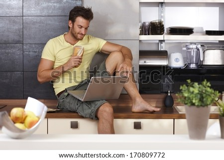 Young man sitting on kitchen counter, having sandwich, using laptop computer.