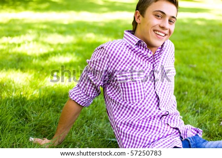 Young man sitting on lawn in park