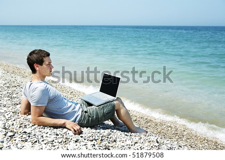 Young man sitting on pebbled beach with laptop