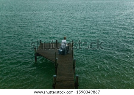 Young man sitting on pier in rain