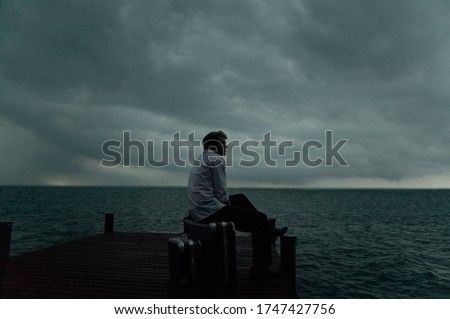 Young man sitting on pier with suitcases in stormy weather