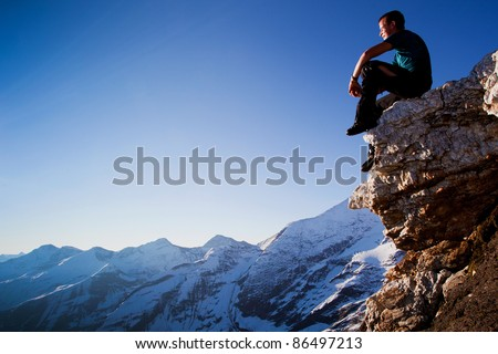 Young man sitting on rock above mountain range