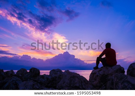 Young man sitting on sea rocks by the beach thinking, contemplating, determining the way forward. Life changing decisions. Priority decision making. Freedom to choose. Passing time as the sun sets. Photo stock ©