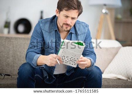 young man sitting on sofa and doing crossword puzzle Foto stock ©