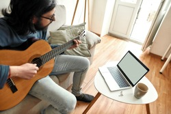 Young man sitting on sofa at home and learning how to play guitar, watching online course on laptop. Distance education. Main focus on laptop. Stay home. E-learning. Music school online