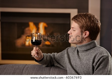Young man sitting on sofa at home on a cold winter day in front of fireplace, tasting red wine.