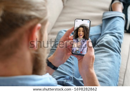 Young man sitting on sofa holding smartphone communicating with african girl friend on mobile screen, making video call using cell phone mobile social media dating app. Video call concept.