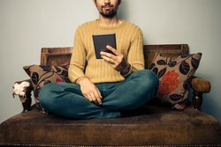 Young man sitting on sofa reading on tablet