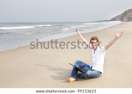 Young man sitting on the beach with laptop arms stretched