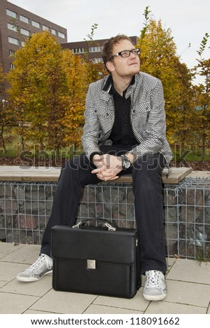 young man sitting on the bench after a working day