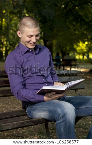 Young man sitting on the bench and reading a book - stock photo