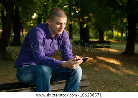 Young man sitting on the bench and writes a message