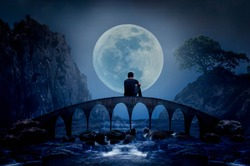 Young man sitting on the bridge watching the full moon on a beautiful night happily.