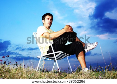 Young man sitting on the chair outdoor