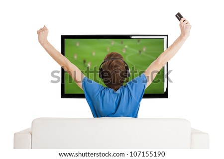 Young man sitting on the couch watching a football game on tv with arms up