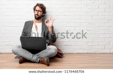 "young man sitting on the floor making an ""alright"" or ""okay"" gesture approvingly with hand, looking happy and satisfied. Positive check sign."