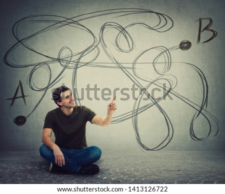 Young man sitting on the floor pointing forefinger finding the correct way from point A to point B. Solving problem, find solution, business idea and creativity concept.