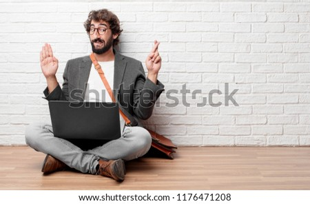 young man sitting on the floor smiling confidently while making a sincere promise or oath, solemnly swearing with one hand over heart.