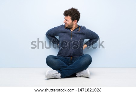 Young man sitting on the floor suffering from backache for having made an effort