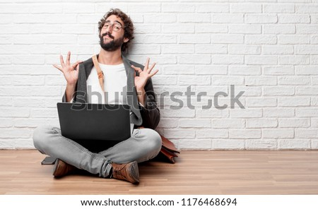"young man sitting on the floor with a proud, happy and confident expression; smiling and sure of success, giving an ""achiever"" look. #1176468694"