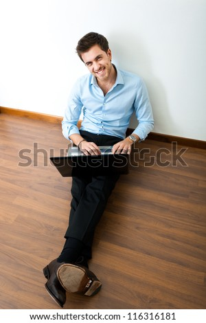Young man sitting on the floor with his laptop