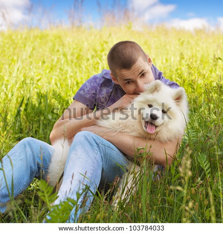 Young man sitting on the grass and playing with white fluffy puppy