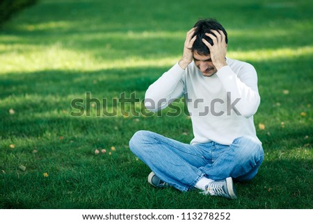 Young man sitting on the grass holding head in frustration